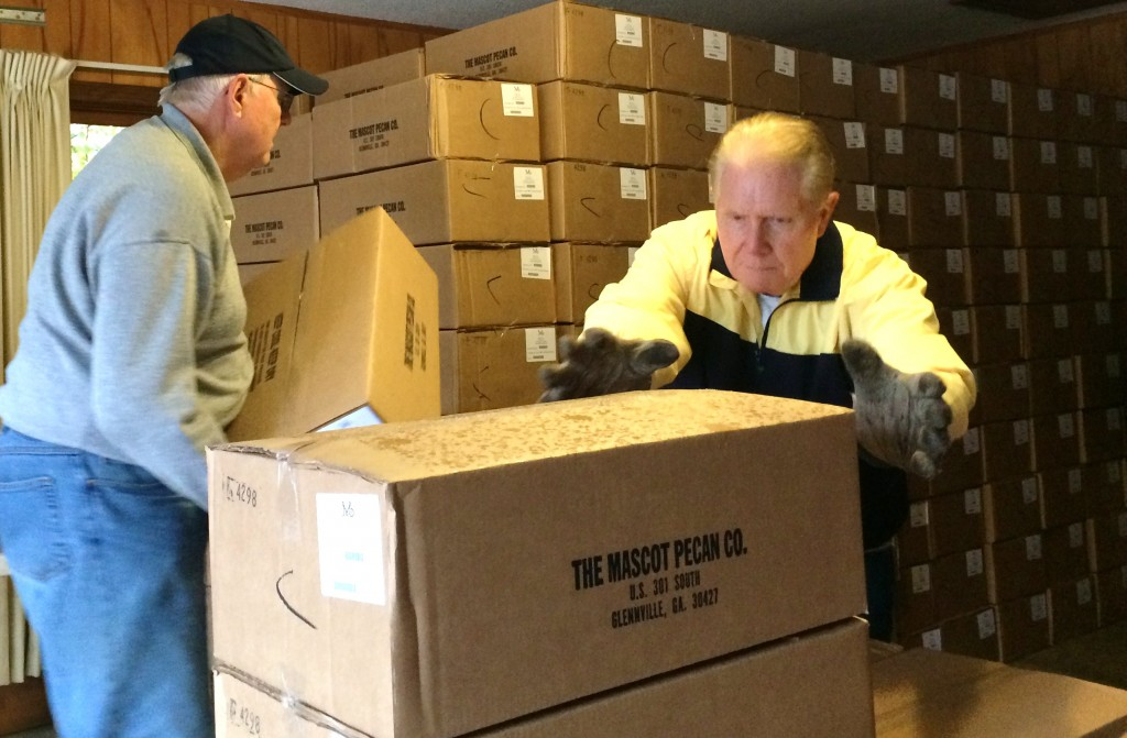 Lakeland Lions Club members Cecil Tompkins and Ron Brandon help stack 1200 cases of pecans for the civic groups annual sale. Staff Photo.