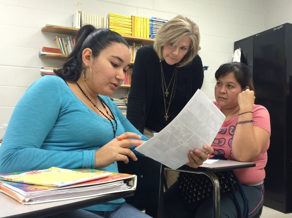 ESL Teacher Michelle Sluder works with Veronica Perez and Luz Velazquez, parents in the municipal school district's adult ESL class. Staff Photo.